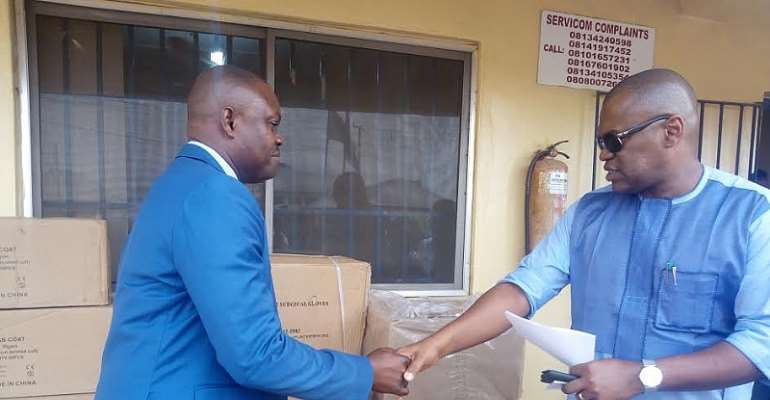 Dr Nicholas Azinge, Commissioner for Health, Delta State in a handshake with Dr Victor A. Osiatuma, during the presentation of the items