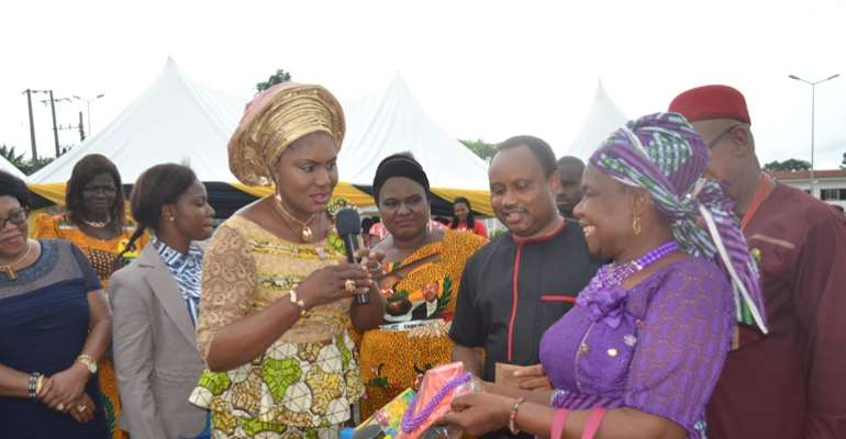 (L-R): Wife of the Governor of Anambra State, Chief (Mrs.) Ebelechukwu Obiano handing over empowerment items to a beneficiary. She is flanked by Special Adviser on Youth Empowerment and Executive Director ANSACA, Dr. Onyeka Ibezim, and His Royal Highness,