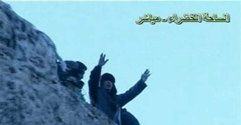 A SHOT TAKEN FROM VIDEO BROADCAST SHOWS EMBATTLED MUAMMAR GADHAFI ADDRESSING HIS SUPPORTERS AT TRIPOLI'S GREEN SQUARE ON FEBRUARY 25, 2011. PHOTOGRAPH BY REUTERS.