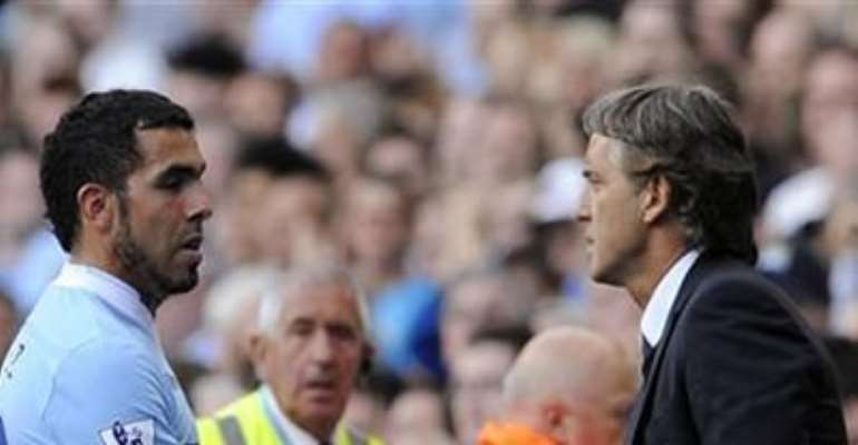 MANCHESTER CITY'S COACH ROBERTO MANCINI (R) SUBSTITUTES CARLOS TEVEZ DURING THEIR ENGLISH PREMIER LEAGUE SOCCER MATCH AGAINST WIGAN ATHLETIC IN MANCHESTER, NORTHERN ENGLAND SEPTEMBER 10, 2011.
