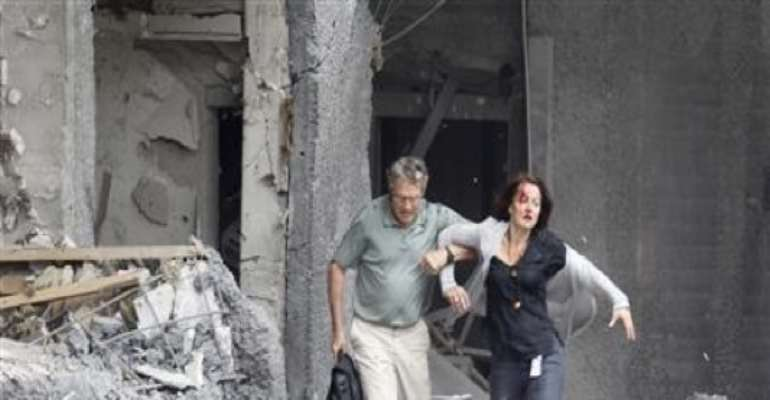 AN INJURED WOMAN IS HELPED BY A MAN AT THE SCENE OF THE EXPLOSION IN CENTRAL OSLO, NORWAY, JULY 22, 2011. CREDIT: REUTERS/MORTEN HOLM/SCANPIX.