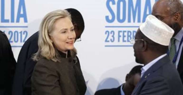 SECRETARY OF STATE HILLARY CLINTON (L) SHAKES HANDS WITH THE PRESIDENT OF SOMALIA, SHEIKH SHARIF AHMED, DURING THE LONDON CONFERENCE ON SOMALIA AT LANCASTER HOUSE IN LONDON FEBRUARY 23, 2012.