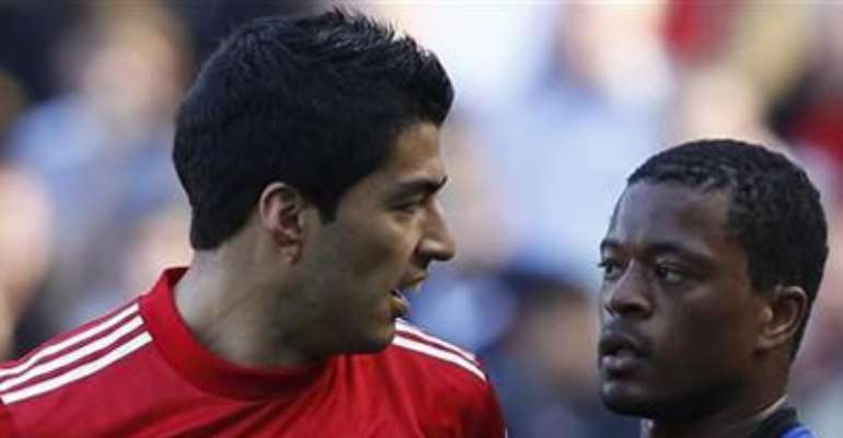 LIVERPOOL'S LUIS SUAREZ (L) AND MANCHESTER UNITED'S PATRICE EVRA EXCHANGE LOOKS DURING THEIR ENGLISH PREMIER LEAGUE MATCH AT ANFIELD, OCTOBER 15, 2011.