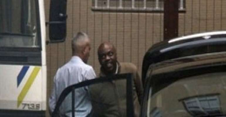 PHOTO: SUSPECTED MASTERMIND OF NIGERIA'S INDEPENDENCE DAY BOMB BLASTS, MR HENRY OKAH ENTERS A POLICE VEHICLE OUTSIDE  A JOHANNESBURG COURT.