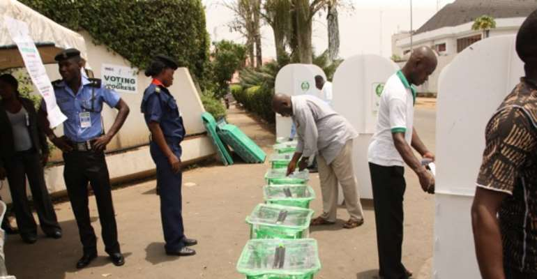 VOTERS CAST THEIR VOTES AS SECURITY AGENTS KEEP WATCH DURING THE PRESIDENTIAL ELECTION IN ABUJA ON APRIL 16, 2011.