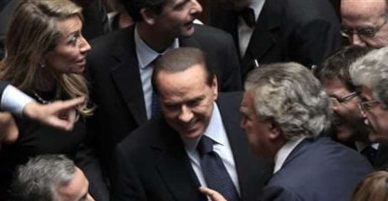 ITALIAN PRIME MINISTER SILVIO BERLUSCONI REACTS NEXT TO NATIONAL COORDINATOR OF THE PEOPLE OF FREEDOM DENIS VERDINI (R) IN THE LOWER CHAMBER OF THE DEPUTIES IN ROME, OCTOBER 14, 2011.