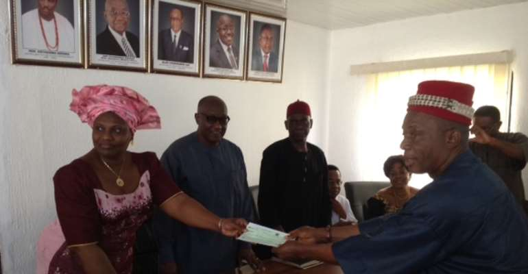 Comissioner of Finance handing a cheque to the Igwe of Ivite Ikem