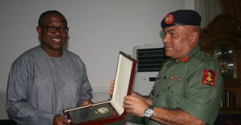 The Director-General of National Youth Service Corps, Brig. Gen. Nnamdi Okorie-Affia (right), making a presentation to Gov. Obi (left), when he paid a visit to the Governor.