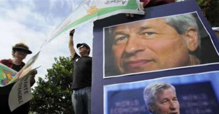 PROTESTORS HOLD SIGNS AND PICTURES OF CEO JAMIE DIMON AS JP MORGAN CHASE & CO CONVENES ITS ANNUAL SHAREHOLDERS MEETING AT THE BANK'S BACK-OFFICE COMPLEX IN TAMPA, FLORIDA, MAY 15, 2012. CREDIT: REUTERS/BRIAN BLANCO