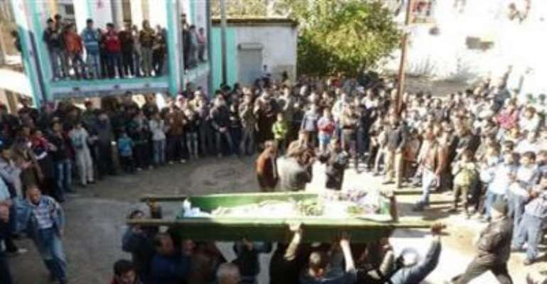 ANTI-GOVERNMENT PROTESTERS CARRY THE COFFIN OF ABDUL HALEEM BAQOUR DURING HIS FUNERAL IN HULA NEAR HOMS DECEMBER 10, 2011.