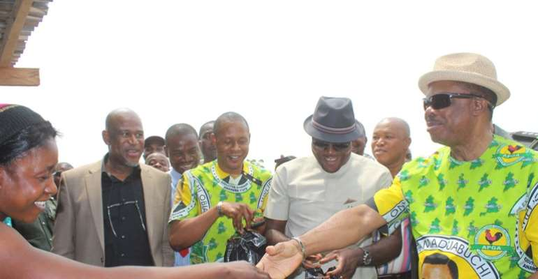 Anambra State Governor, Chief Willie Obiano in a handshake with Madam Awele, the dry fish seller across Ezu Bridge in Ayamelum Local Government Area.
