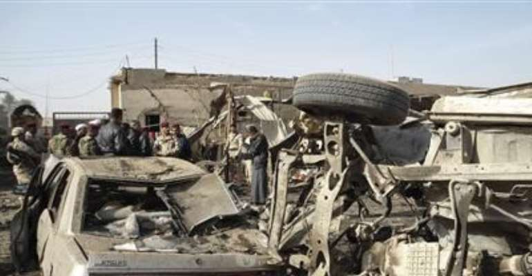 IRAQI SOLDIERS INSPECT THE SITE OF A BOMB ATTACK IN KHALIS, 65 KM (40 MILES) NORTHEAST OF BAGHDAD, DECEMBER 1, 2011.