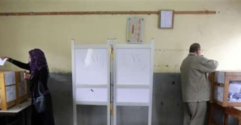 A MAN AND A WOMAN CAST THEIR VOTES IN A SCHOOL USED AS A VOTING CENTER IN AL-ARISH CITY, NORTH SINAI, JANUARY 4, 2012.