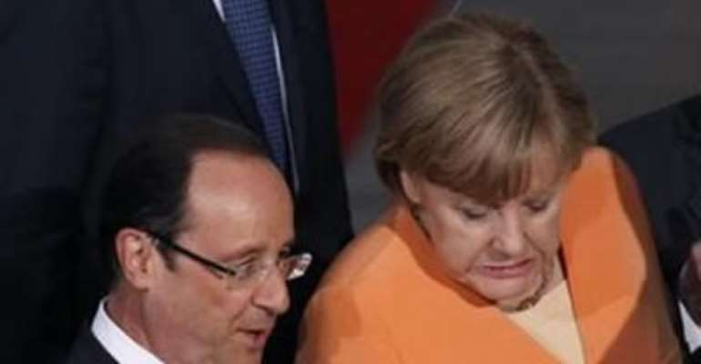 GERMAN CHANCELLOR ANGELA MERKEL (C) GRIMACES AS SHE STEPS OFF A STAGE FOLLOWING A FAMILY PHOTO WITH NATO LEADERS INCLUDING FRENCH PRESIDENT FRANCOIS HOLLANDE (L) AT SOLDIER FIELD IN CHICAGO, MAY 20, 2012.