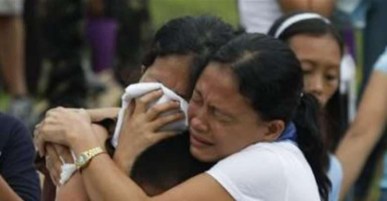 RELATIVES MOURN DURING A MASS BURIAL FOR TYPHOON WASHI VICTIMS IN A CEMETERY IN ILIGAN CITY, SOUTHERN PHILIPPINES DECEMBER 20, 2011.