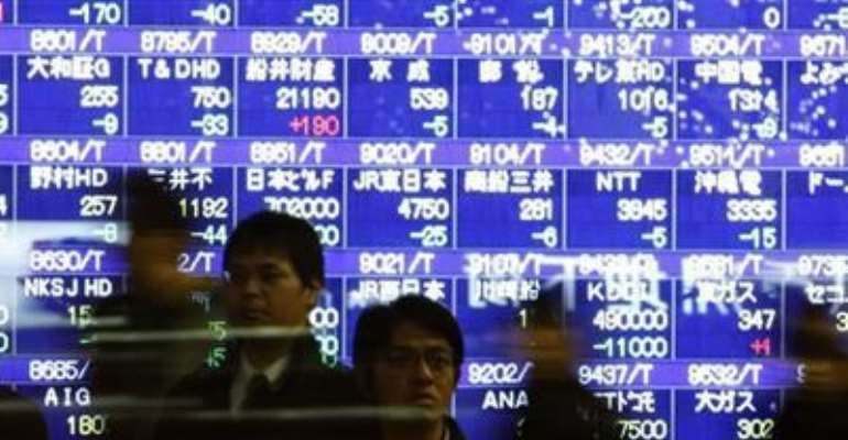 PASSERS-BY WALK IN FRONT OF A STOCK QUOTATION BOARD IN TOKYO DECEMBER 9, 2011.