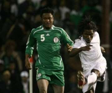 Ghana's Laryea Kingson, right, strikes the ball as Nigeria's Jon Obi Mikel, left, standing looking, during their International friendly soccer match at Griffin Park Stadium, London, Tuesday Feb. 6, 2007. (AP Photo/Graham Hughes )